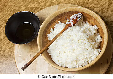 Rice - A big wooden cup with spoon full of rice