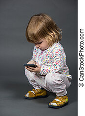 Cute little baby with father's mobile phone, smartphone