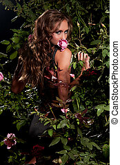 woman standing among the rose bushes - an attractive woman...