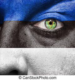 Flag painted on face with green eye to show Estonia support