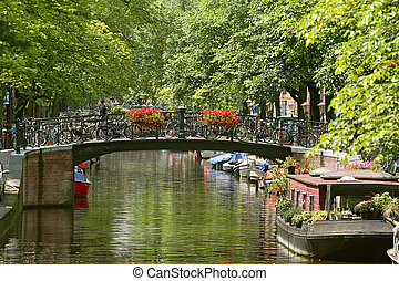 Amsterdam cityscape. - View on small bridge with flowers and...