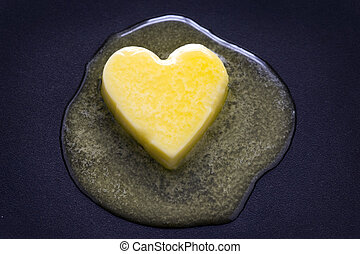 butter heart melting - a heart shaped butter pat melting on...