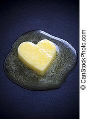 butter heart melting - a heart shaped butter pat melting on...