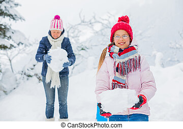 Winter girl throwing snowball with mother - Smiling happy...
