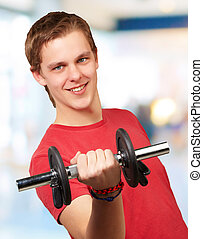 portrait of young man with weights in indoor