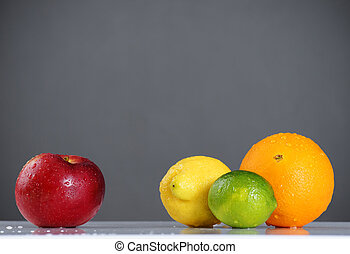 Apple compared to citrus fruits over grey - Different or...
