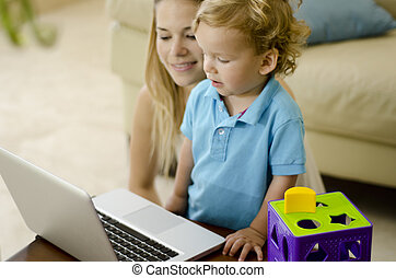Cute boy learning to use a computer with his mother