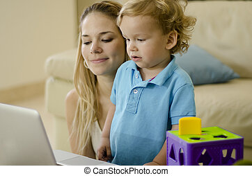 Mom and son watching cartoons - Young mother and her son...