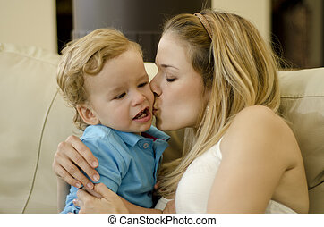 Young mom kissing her son