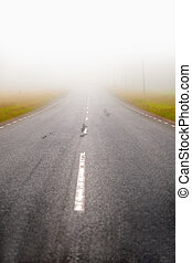asphalt road in fog - rural asphalt road disappearing into...