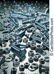 Metal tools - Screws, nuts, washers on a metal table.
