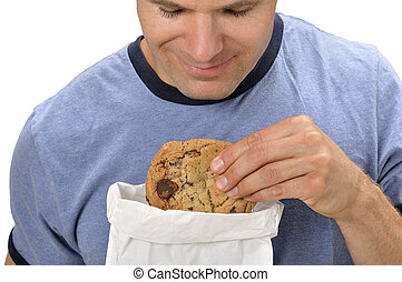 Craving a cookie - Closeup of man taking a big chocolate...