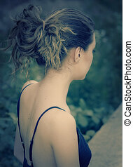 Young woman's back in romantic light outdoor in summer.