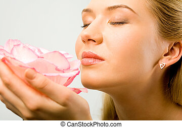 Fine aroma - Portrait of beautiful woman holding a flower...