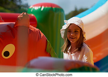 Cute little girl in a jumping castle - Pretty young girl...