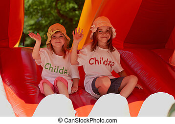 Cute little sisters in a jumping castle