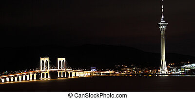 Cityscape in night with famous travel tower near river in...