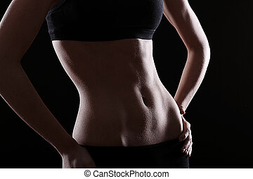 Slim and sexy stomach on black background