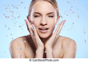 Beautiful woman washing her face - Young and beautiful woman...