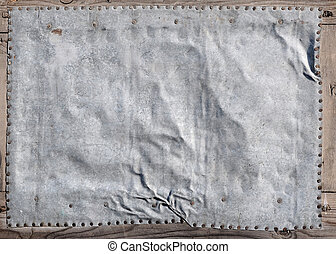 empty aged metal plate on wooden background