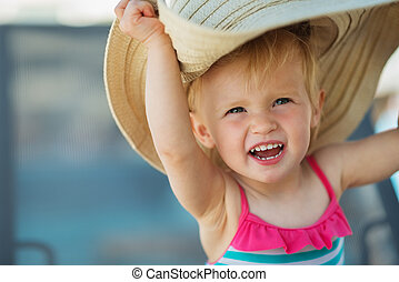 Portrait of excited baby in beach hat