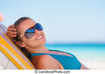 Smiling woman laying on beach
