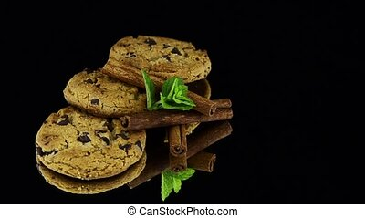 Chocolate cookies with green mint leaves rotating on black...