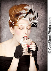 Redhead girl with Rococo hair style and cake in studio at vintage background. Photo in old style.