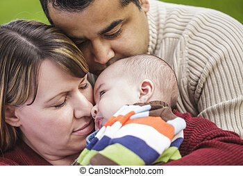 Happy Mixed Race Parents Hugging Their Son in the Park