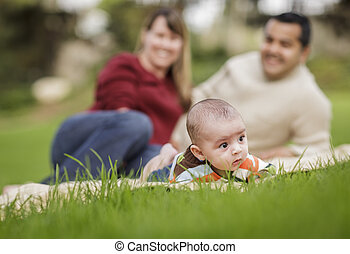 Happy Mixed Race Baby Boy and Parents Playing in Park
