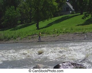 Fisherman on River Bank at Dam - Man fishing on river bank...