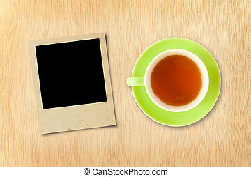cup tea and photo frame on wood background