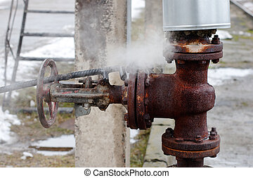 large rusty valve is broken. The steam comes out of the...