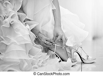 Wedding shoes - The bride is putting on her shoes for the...