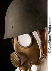 Military person in gas mask and helmet on black background
