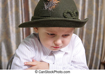 Offended - Boy in hat with feather looking offended