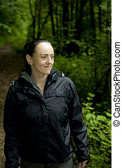 smiling woman in woodland - smiling woman walking on...
