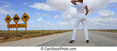 Sexy woman on outback highway - A sexy woman standing on a...