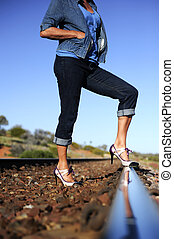 Sexy lady on railway track - Sexy legs of a woman standing...