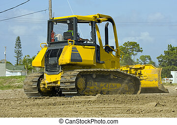 Bulldozer in action - A bulldozer scrapes off the job site