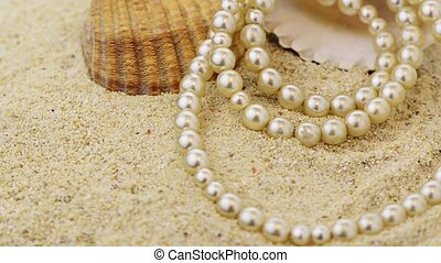 Pearls necklace on sand - Pearls necklace on beach sand with...