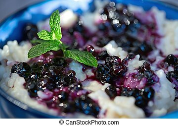 Rice pudding with blueberries in the blue bowl Selective...