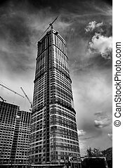 building in a construction stage with cranes against the...