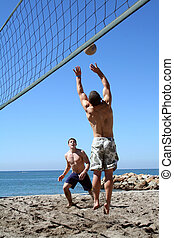 Beach Volleyball - Young men playing volleyball on the beach