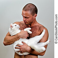 Muscular man holding white cat. On grey background.