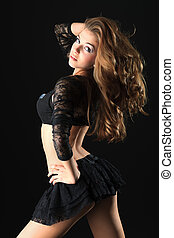 energy - Beautiful girl cheerleader posing at studio. Black...