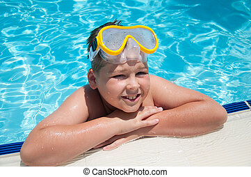 Boy with a mask for snorkeling in the pool