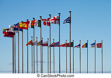 Flags of different countries are developing on the flagpoles...