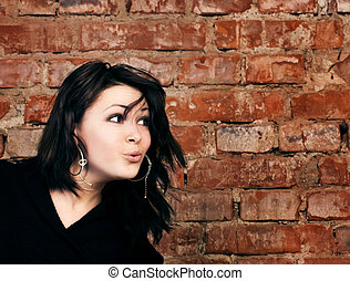 Surprised young girl on brick wall background