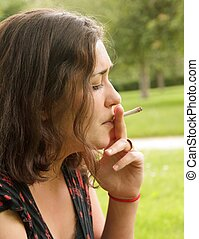 woman smoking a rolled cigare - young woman smoking a rolled...